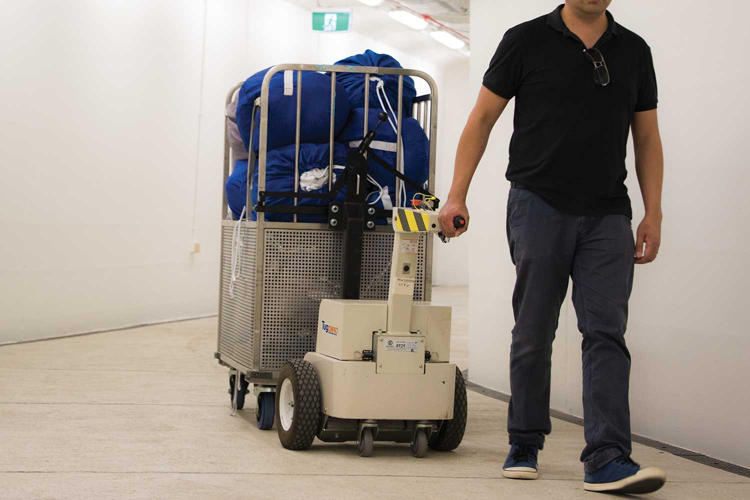 Electrodrive's Tug Compact towing linen trolleys in a hospital